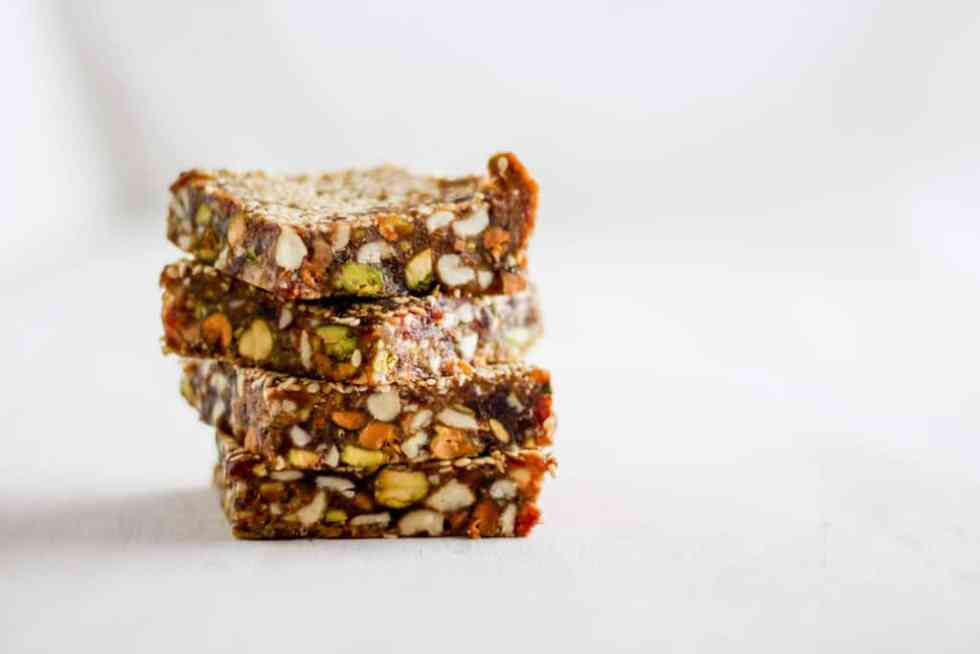 Stack of sesame date bars against white backdrop.
