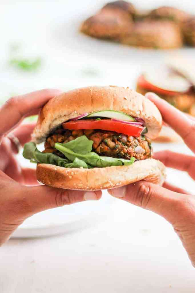 Moroccan Chickpea Burger held in hands with white backdrop.