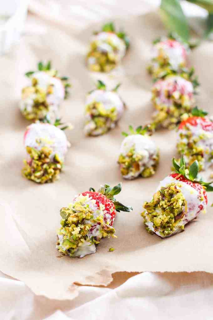 yogurt dipped strawberries with pistachios on parchment paper.