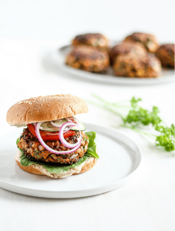 Straight-on shot of Moroccan-spiced chickpea burger on a bun on a white plate with burger patties and herbs in the background.