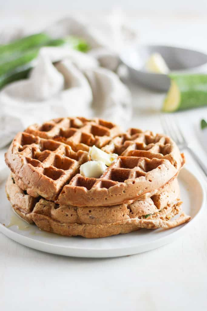 Stack of whole wheat zucchini bread waffles with butter on a white plate with zucchini in background.
