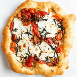 Homemade pizza with caprese toppings against white backdrop.
