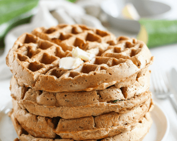 Stack of whole wheat zucchini bread waffles topped with butter on a white plate.