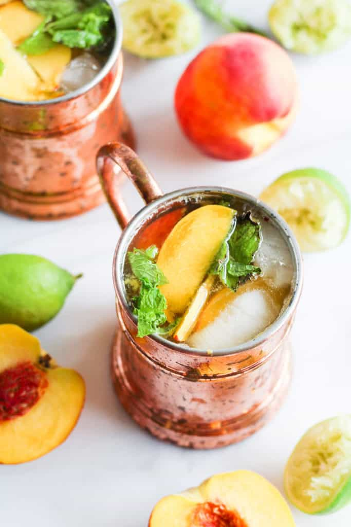Overhead shot of ginger peach kombucha moscow mule in copper mugs on white marble with peaches and lime.