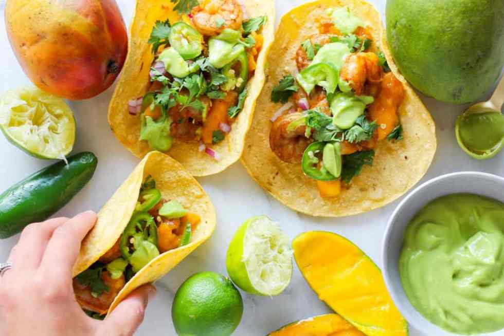 Grilled Mango Shrimp Tacos with hand grabbing a taco. Mango, lime, and jalapeno are also arranged against a white backdrop.