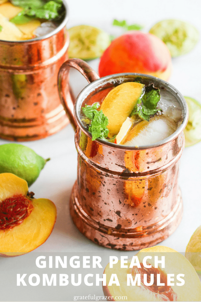 """Ginger peach kombucha Moscow mule in copper mug on white marble surrounded by peaches and lime. Title text reads, """"Ginger Peach Kombucha Mules."""""""