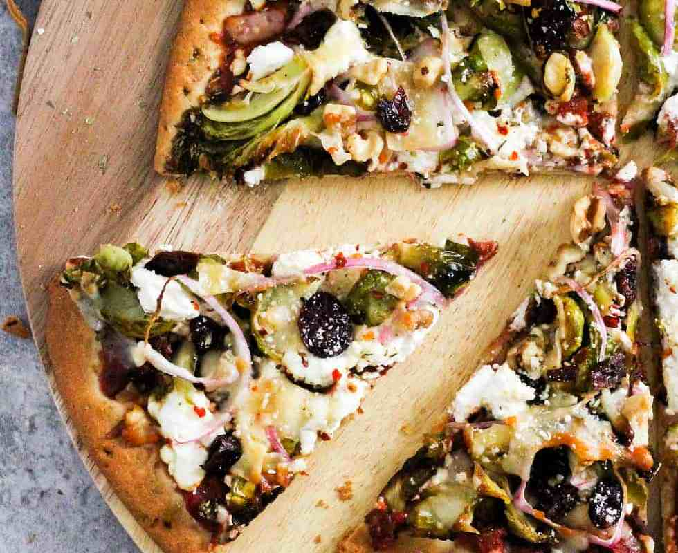 Sliced brussels sprouts pizza on wood serving board.
