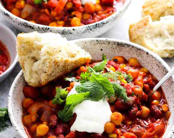 Bean chili with harissa in white stoneware bowl with yogurt and herbs on top.