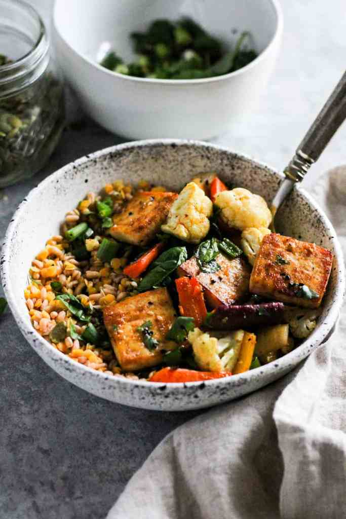 Sheet pan tofu bowls in white stone bowl with herbs and pumpkin seeds in background.