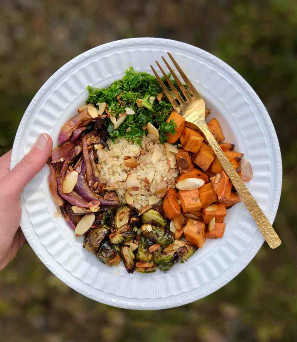 Food trends like seasonal buddha bowl held in hand on white plate with gold fork.