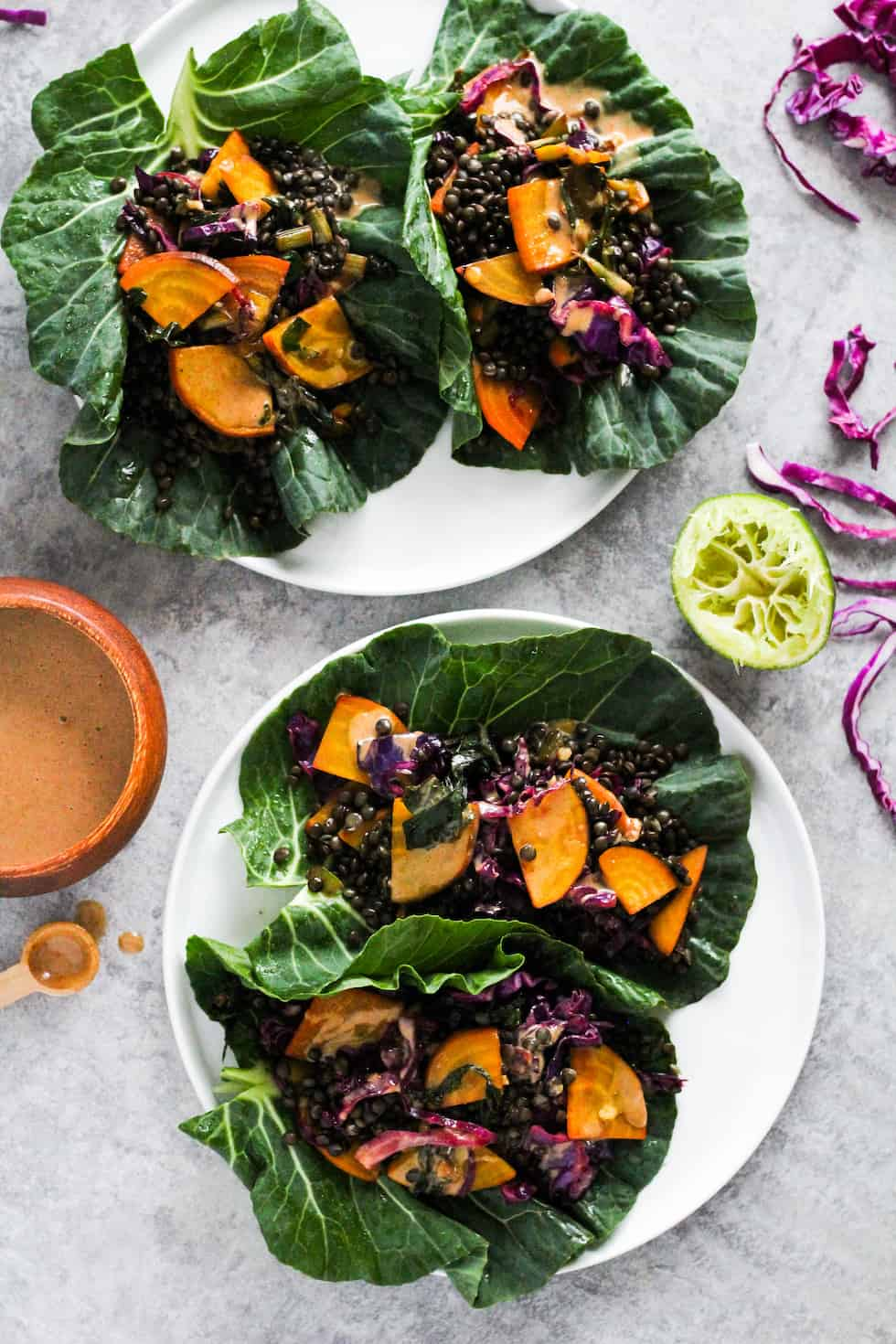 Black lentil collard wraps on white plates with almond sauce and shredded purple cabbage.
