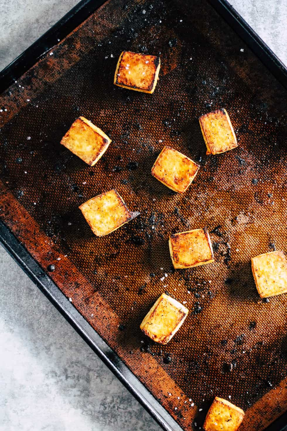 Crispy tofu on sheet pan against grey background.