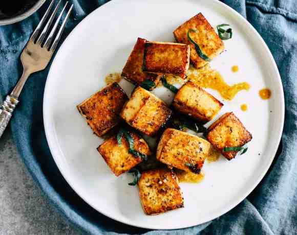 Crispy tofu on white plate with blue linen napkin against grey background.