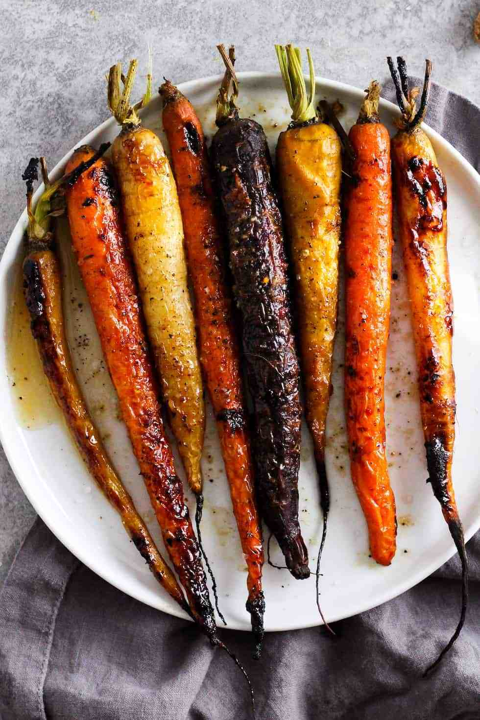Roasted rainbow carrots on white plate. Choosing produce with a long shelf life is one of the best food waste solutions.