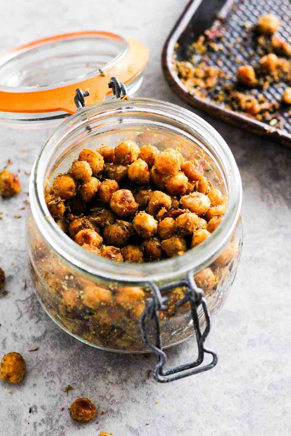 Jar of roasted chickpeas as example of pantry ingredients with baking sheet in the background.