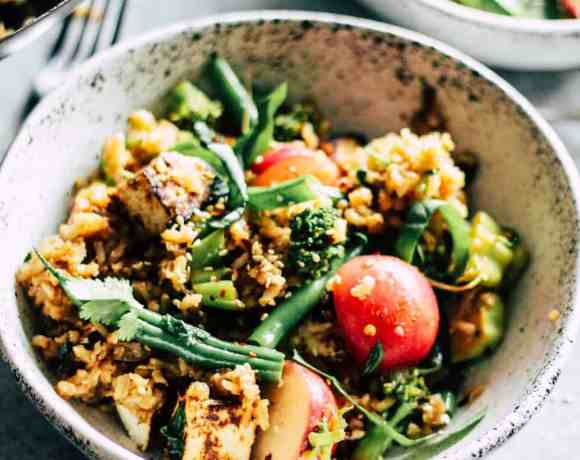 Veggie fried rice in white stone bowl with radishes and green beans.