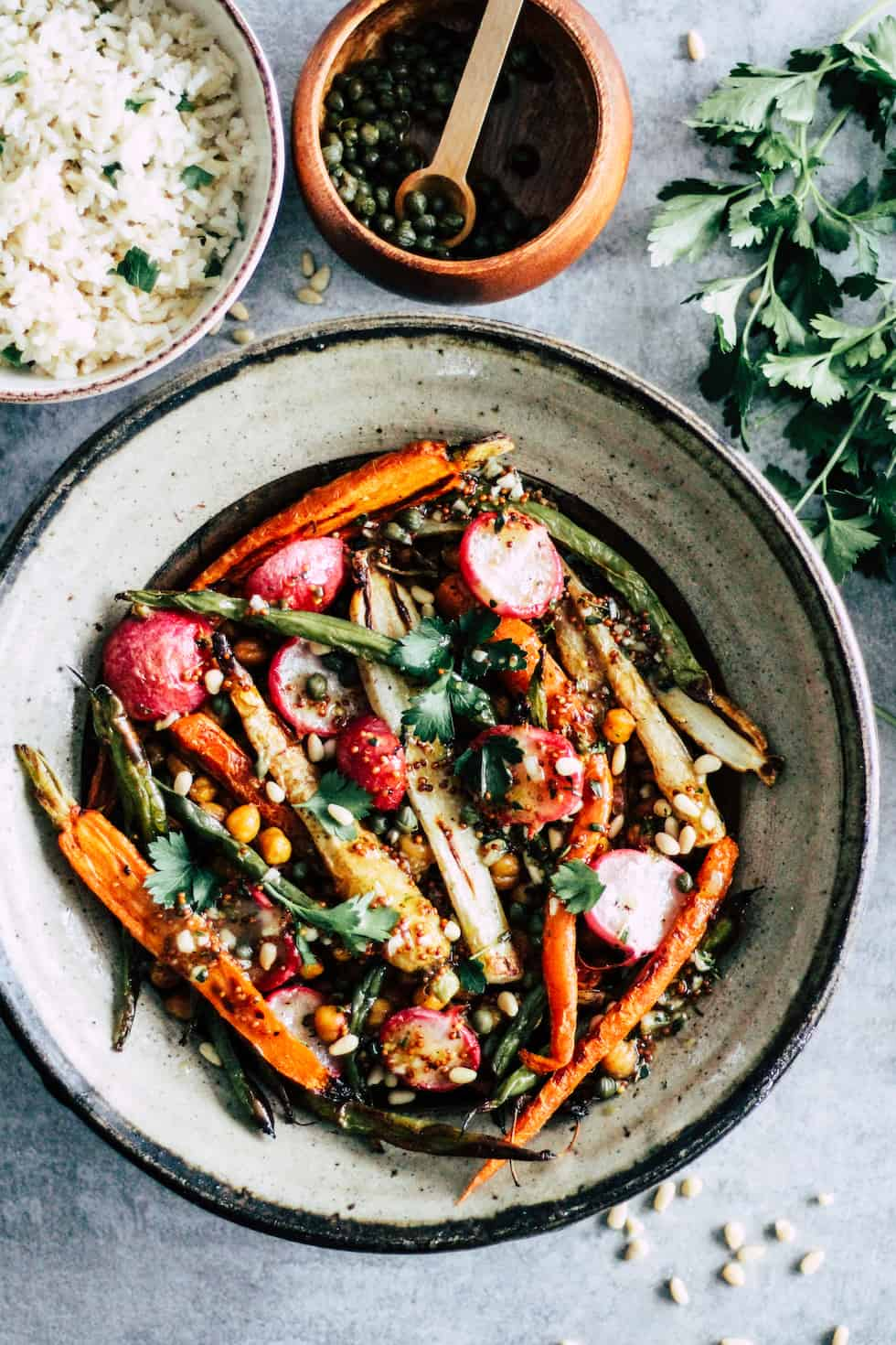 Chickpeas, carrots, and green beans in a stone bowl with smaller bowl of rice and herbs.