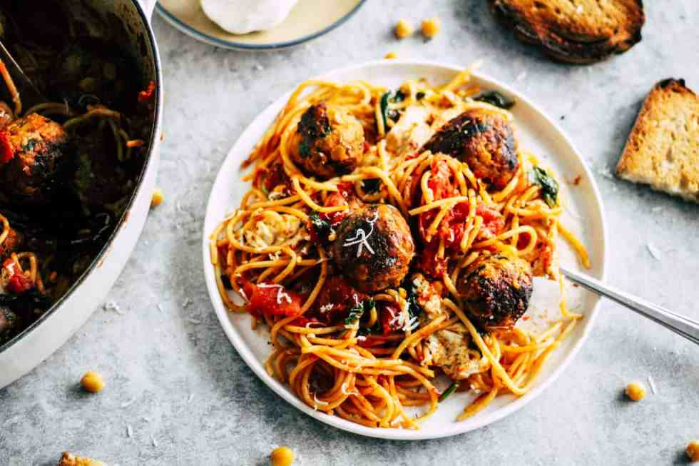 Spaghetti and meatballs on white plate with toasted bread on the side.