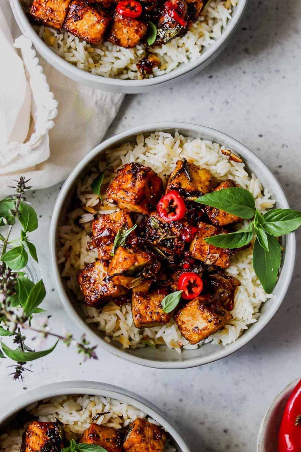 Vegetarian dinner recipes include this black pepper tofu served over rice with fresh basil in a grey bowl.
