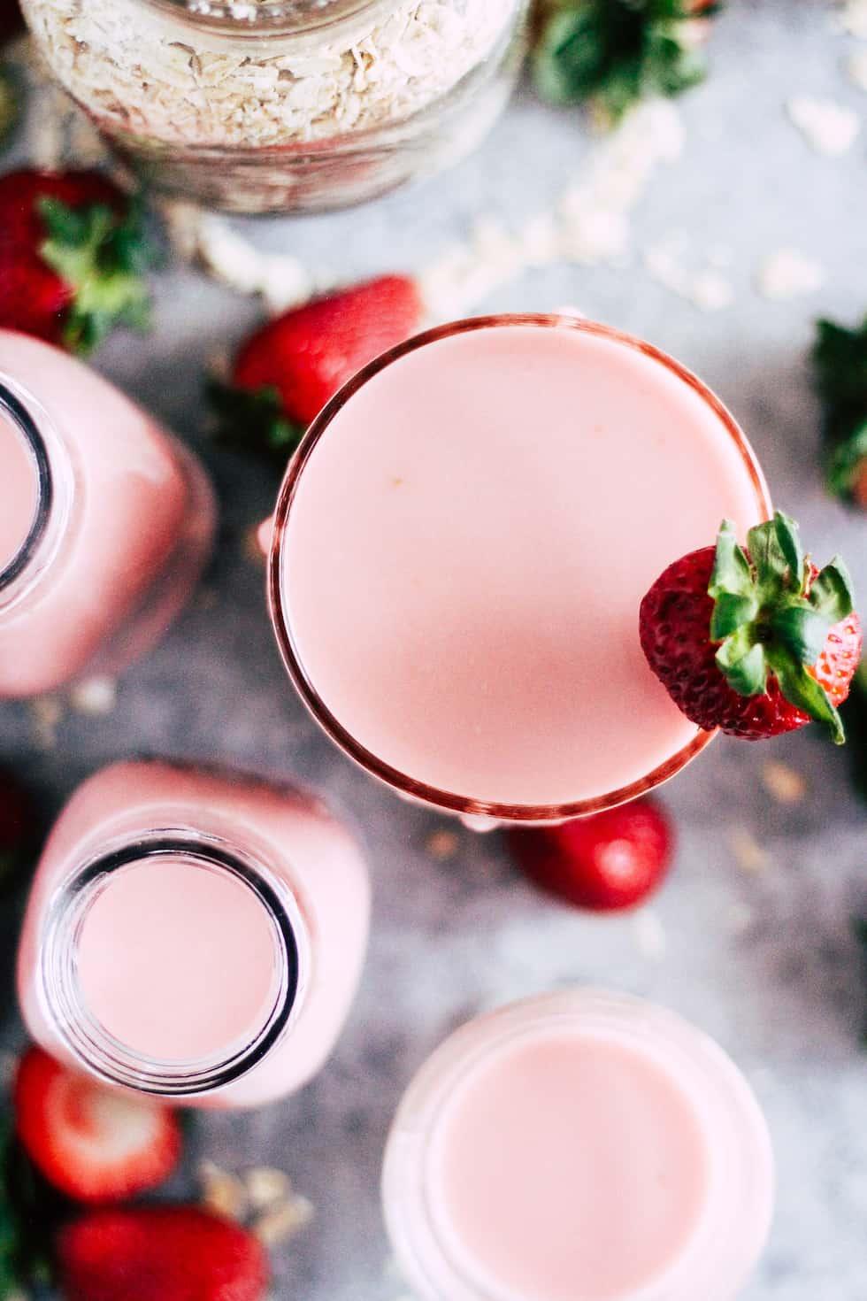 Overhead shot of strawberry oat milk against grey background.