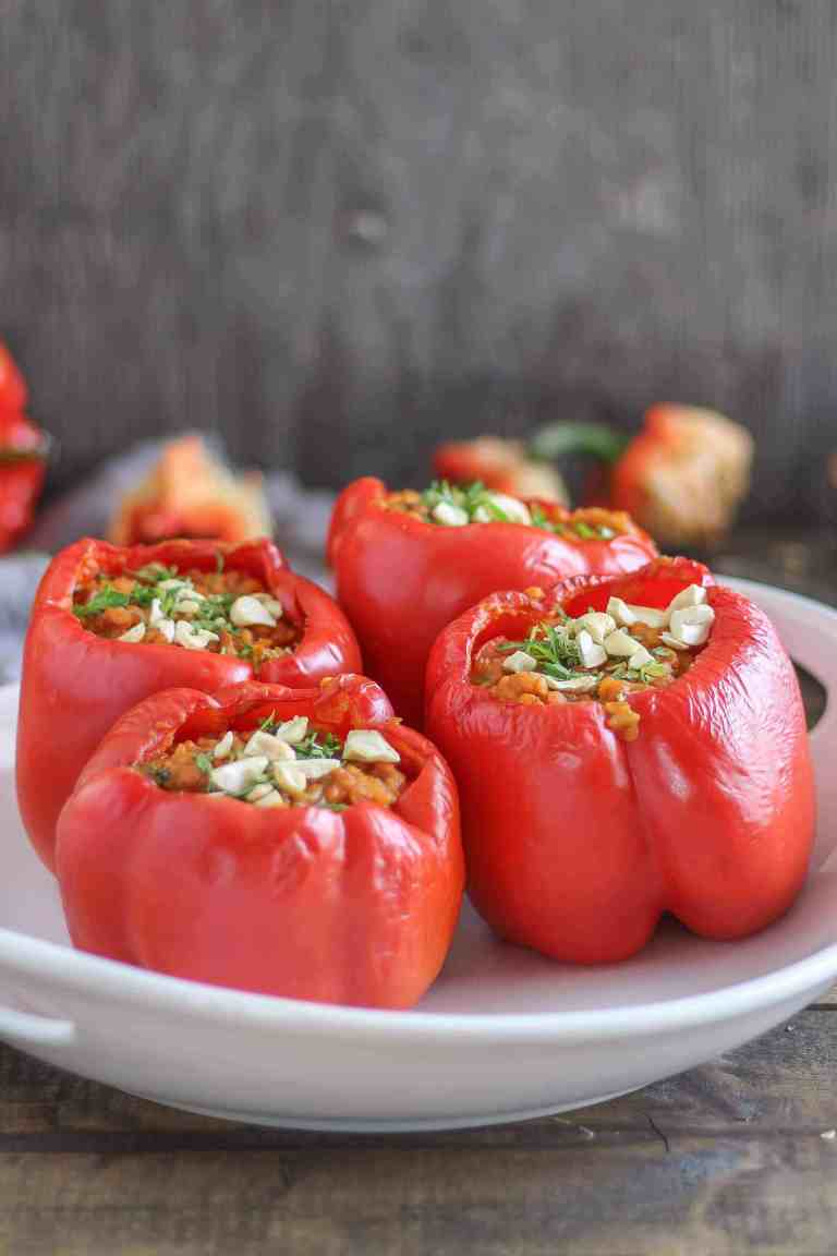 Stuffed red bell peppers on a white platter with grey background.