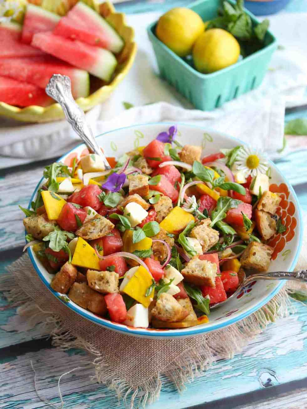 Watermelon panzanella salad in blue bowl with watermelon and carton of lemons in background.