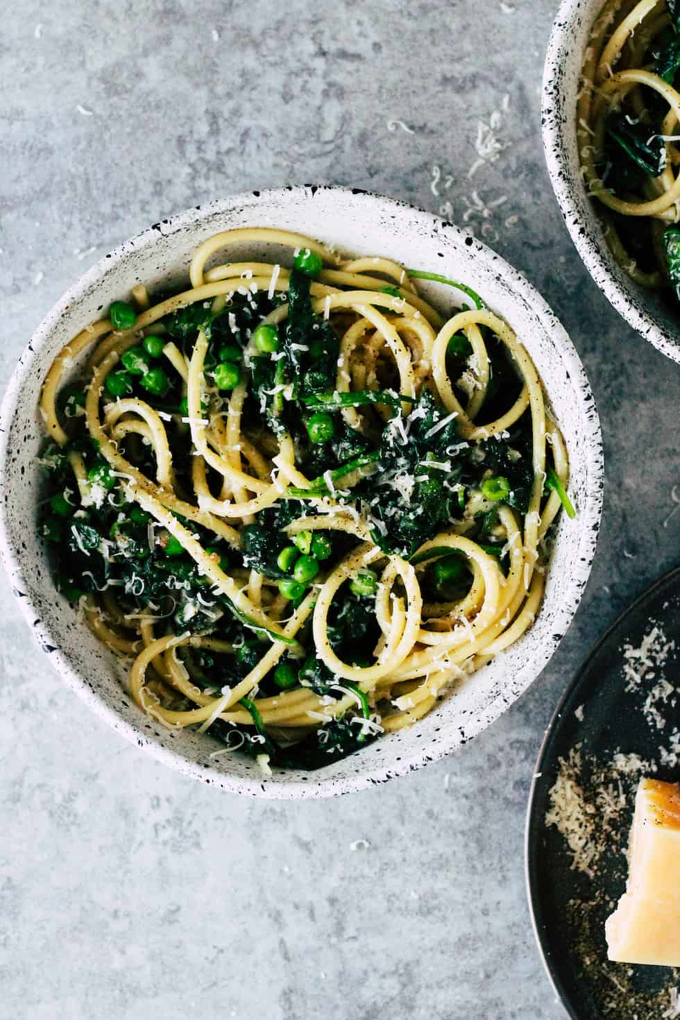 Pasta with spinach and green peas against grey background.