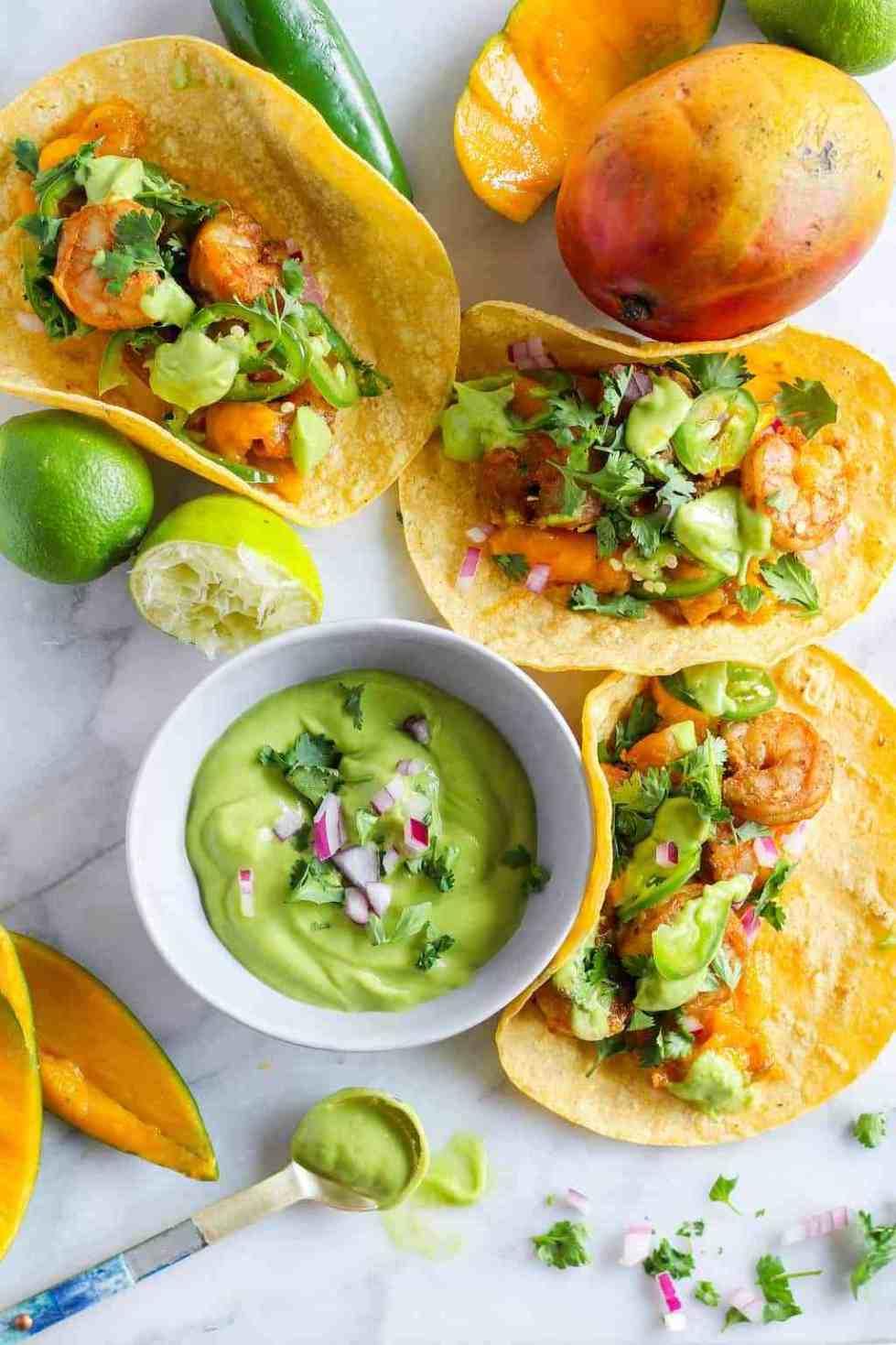 Grilled shrimp mango tacos with small bowl of green avocado sauce.
