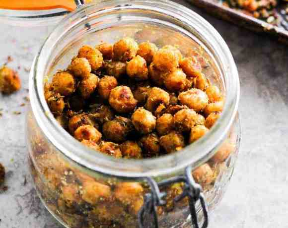 Mason jar filled with roasted chickpeas with baking pan in background.