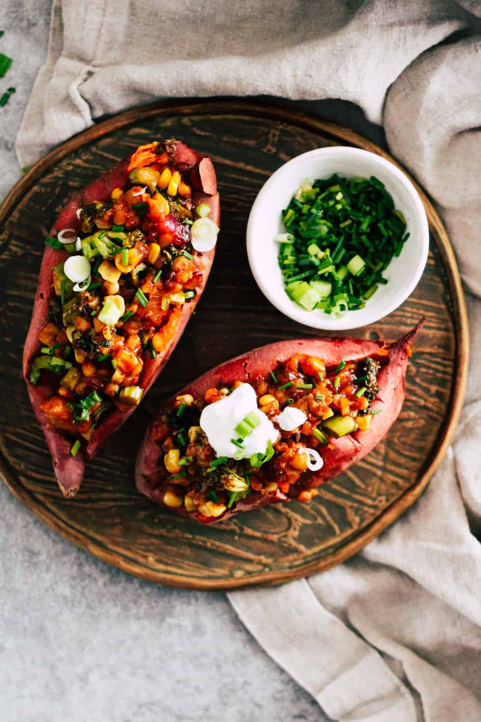Stuffed sweet potatoes on wood plate with small bowl of chives and green onion.