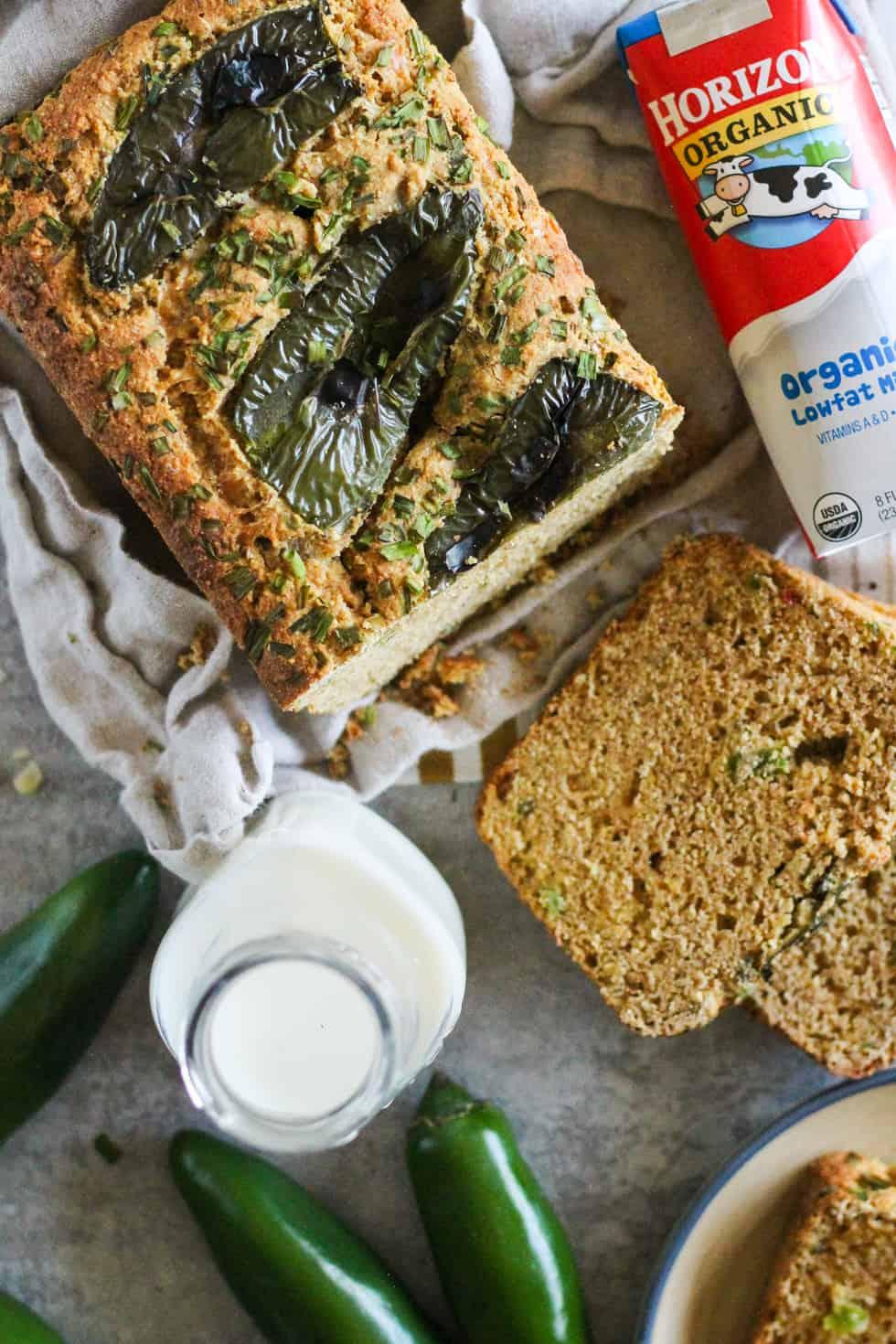 Whole Grain Cornbread Loaf with jalapeños on top. Milk jug and carton of Horizon Organic milk next ot the bread.