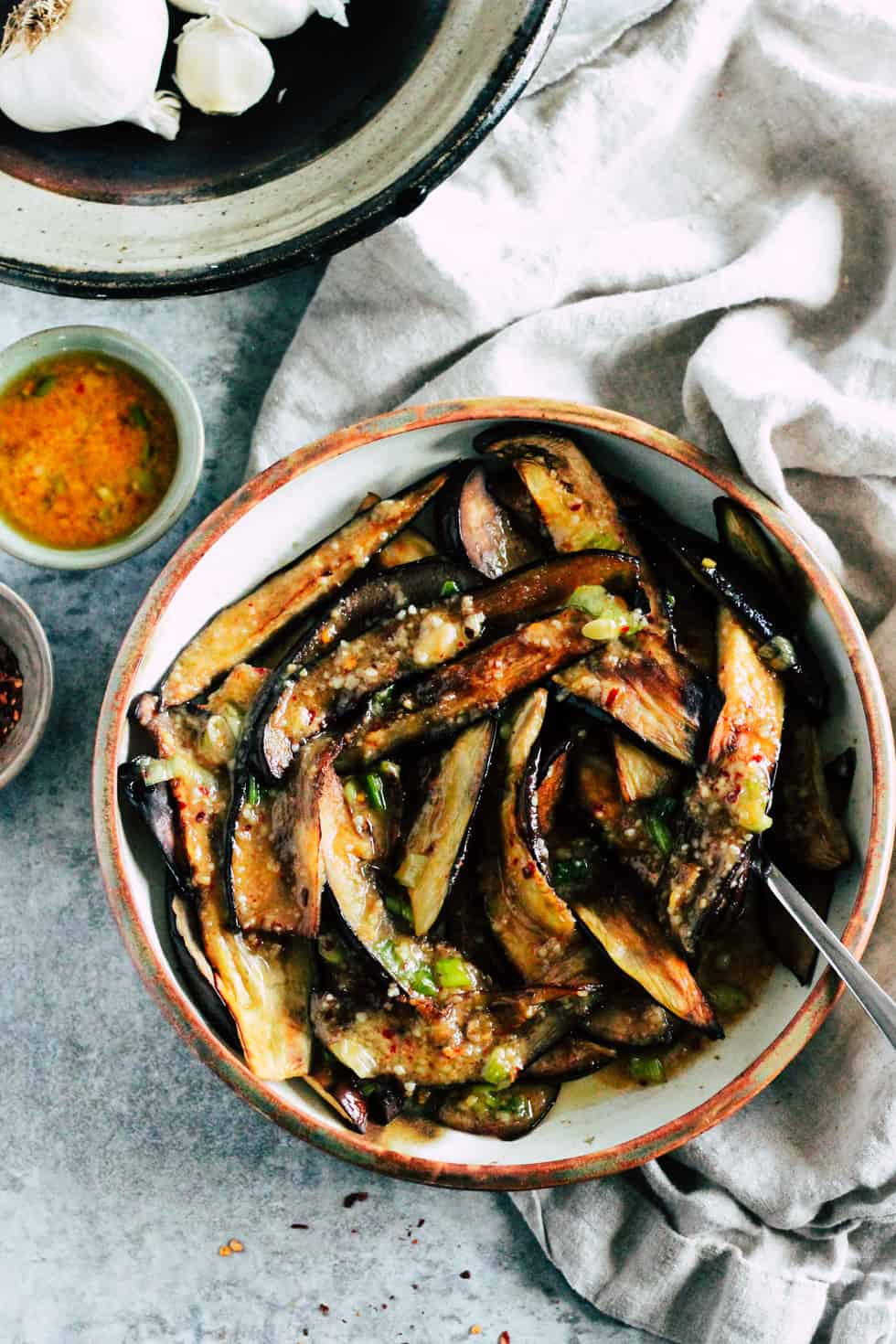 Roasted eggplant in ceramic dish with bowl of brown butter miso sauce and garlic.