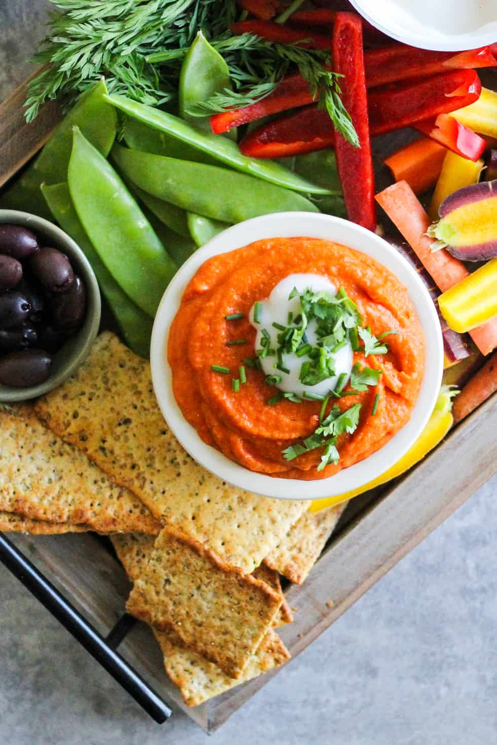 Party board with orange dip and vegetables.