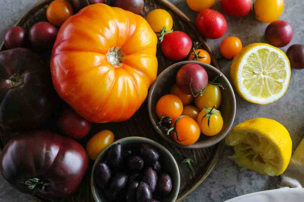 Horizontal image of multicolor heirloom tomatoes with cherry tomatoes and kalamata olives.