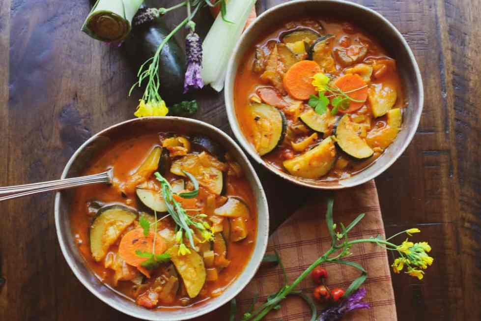 Vegan soup recipes in white bowls against wood background.