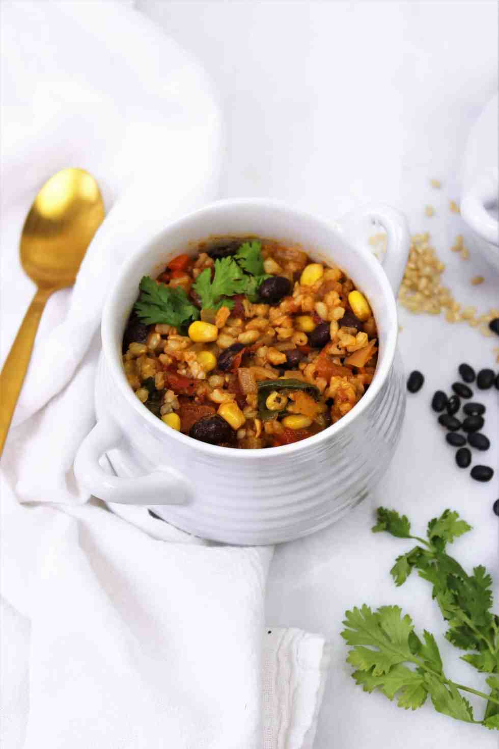 Southwest vegan soup recipes in white crock with gold spoon.