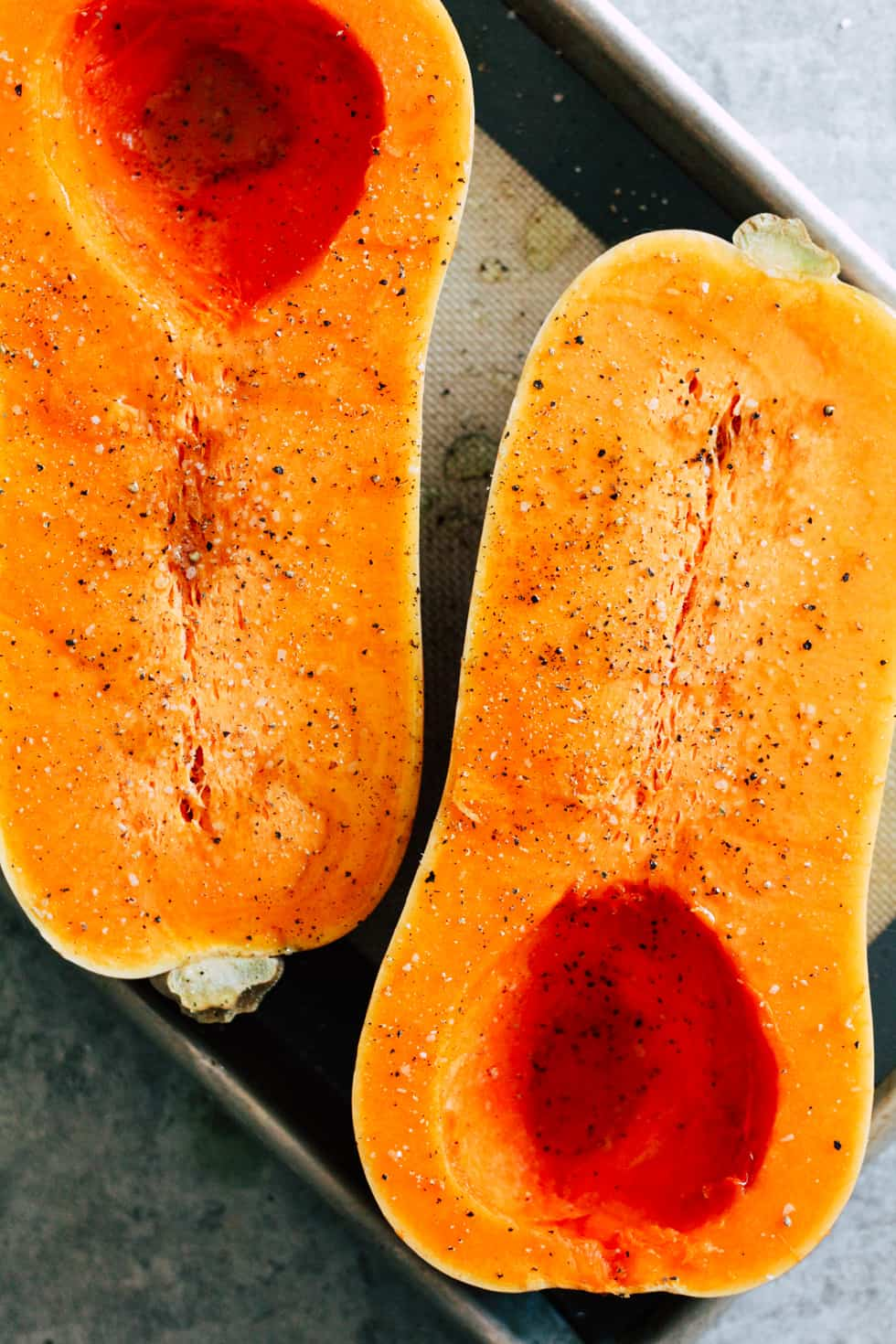 Halved butternut squash on baking sheet.