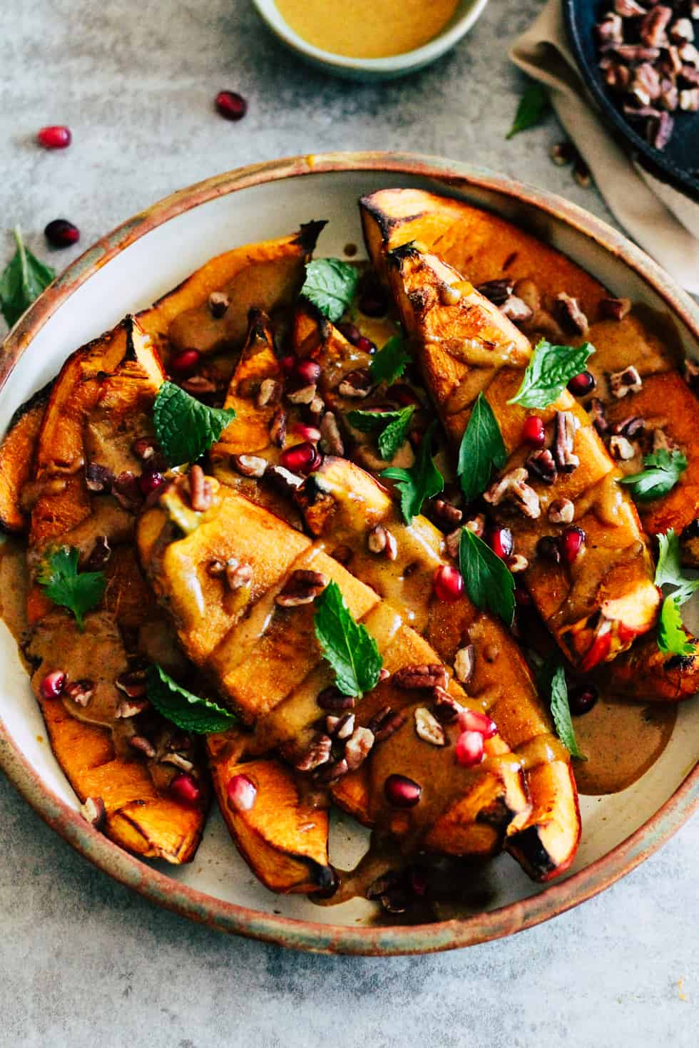 Roasted pumpkin with pomegranate, nuts and herbs in ceramic dish.