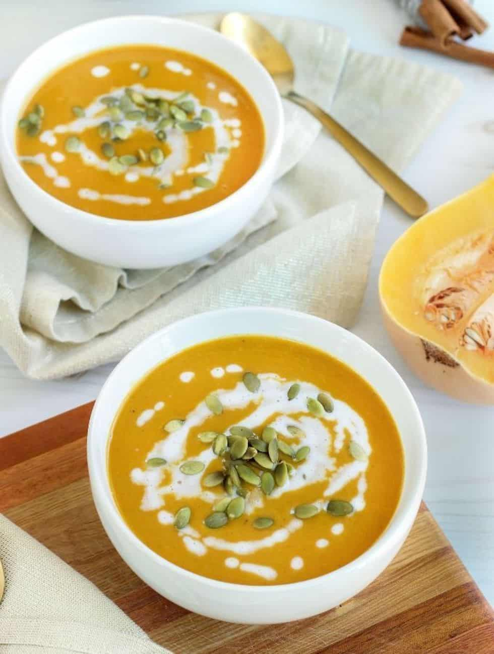 Squash soup in white bowls with sour cream swirl.