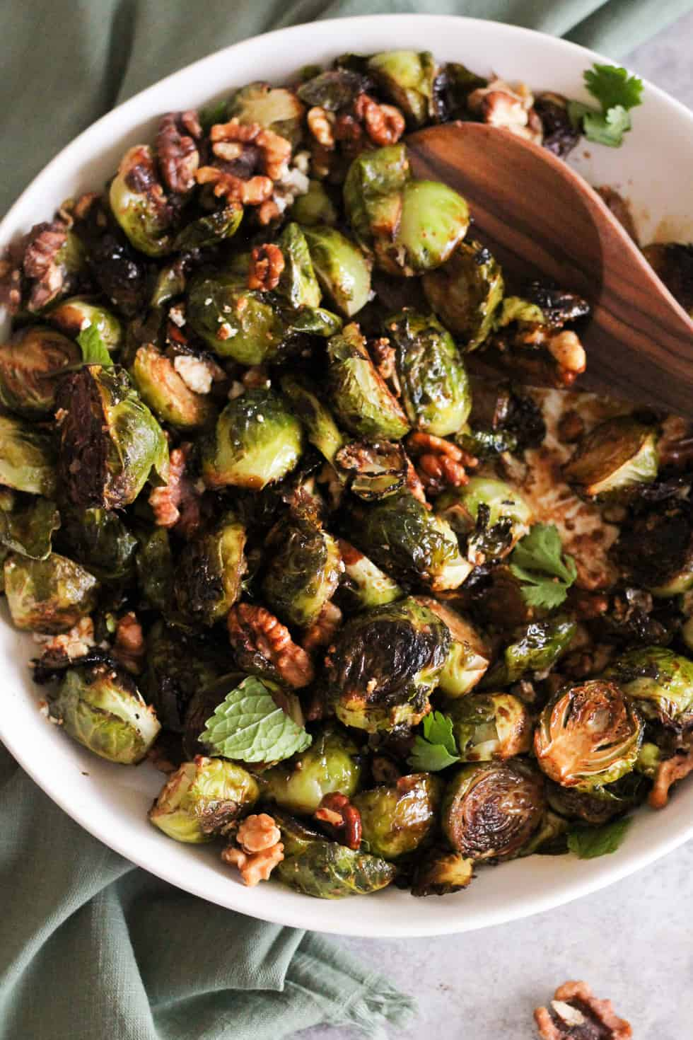 Closeup image of crispy roasted brussels sprouts in white dish with wooden spoon.
