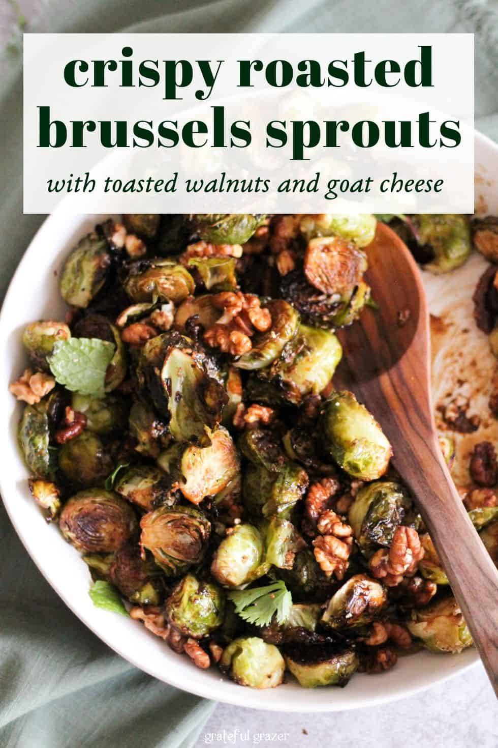 "Brussels sprouts and walnuts in white dish with wooden spoon. Text reads, ""Crispy Roasted Brussels Sprouts with Toasted Walnuts and Goat Cheese."""