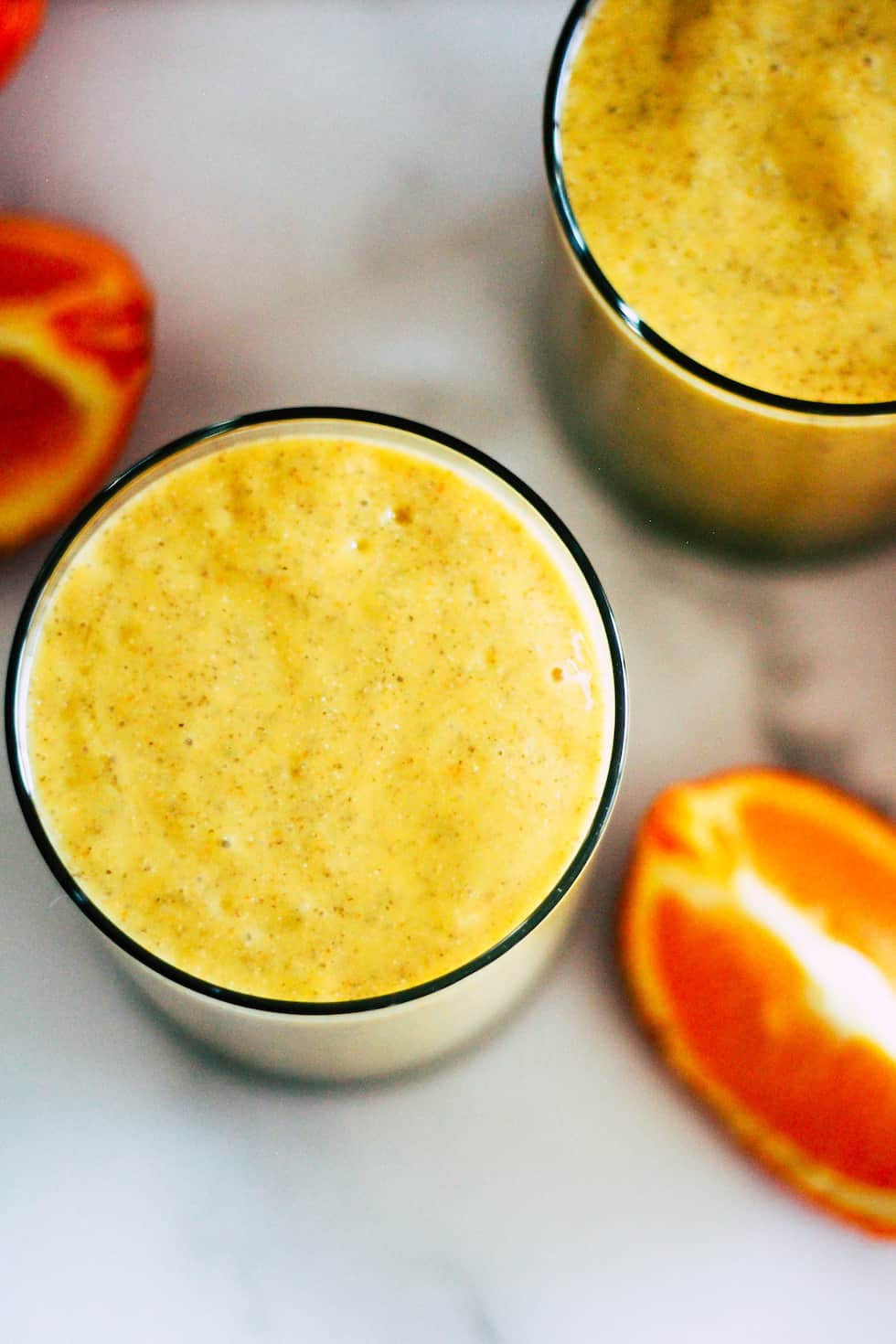 Overhead shot of a smoothie with orange wedges.