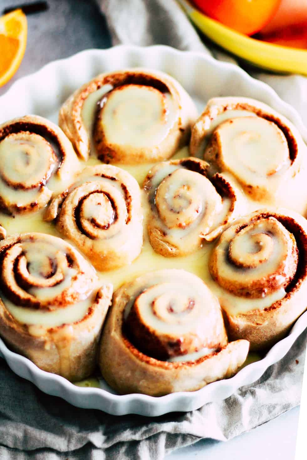 Cinnamon rolls in a round, white baking dish with oranges in the background.