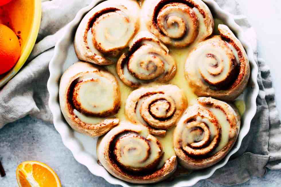 Horizontal image of sweet rolls in a white round baking dish.