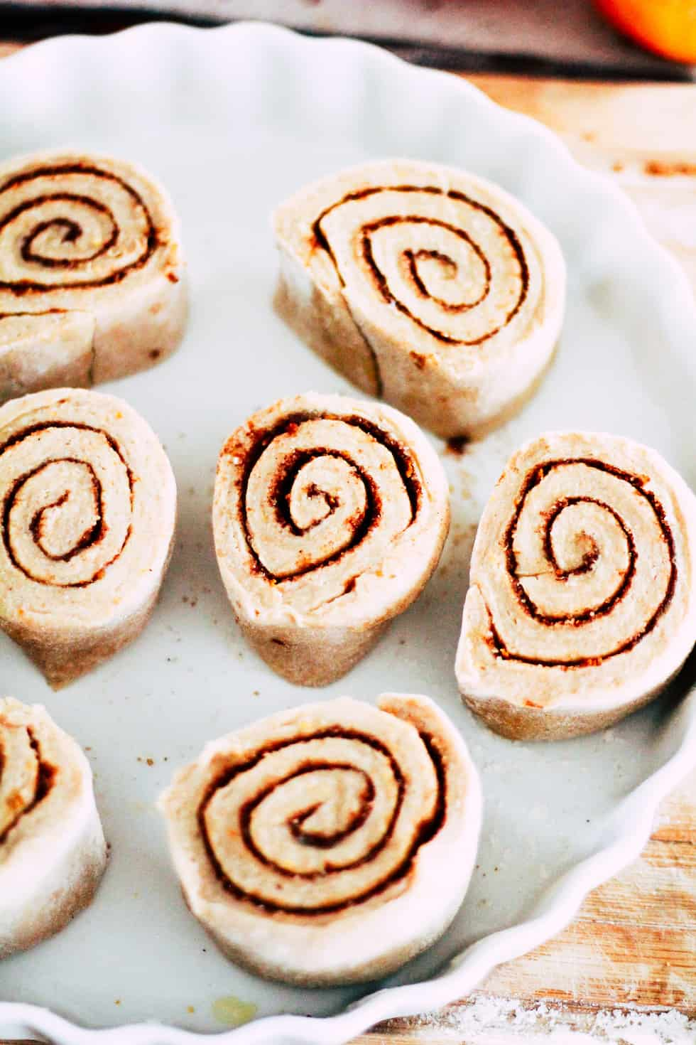 Uncooked cinnamon rolls in a white baking dish.