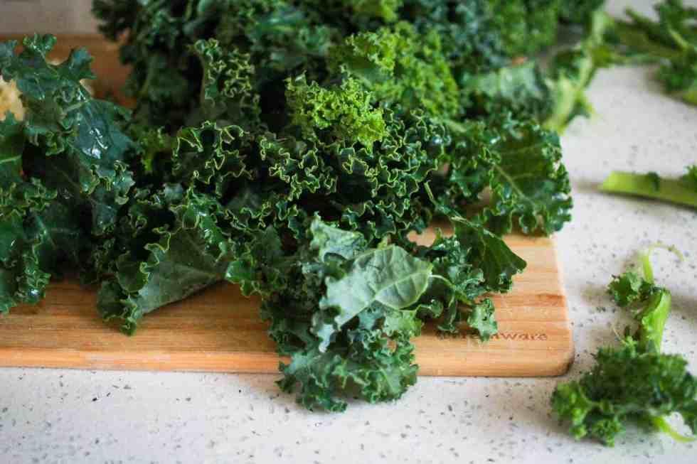 Torn fresh kale on a wood cutting board.