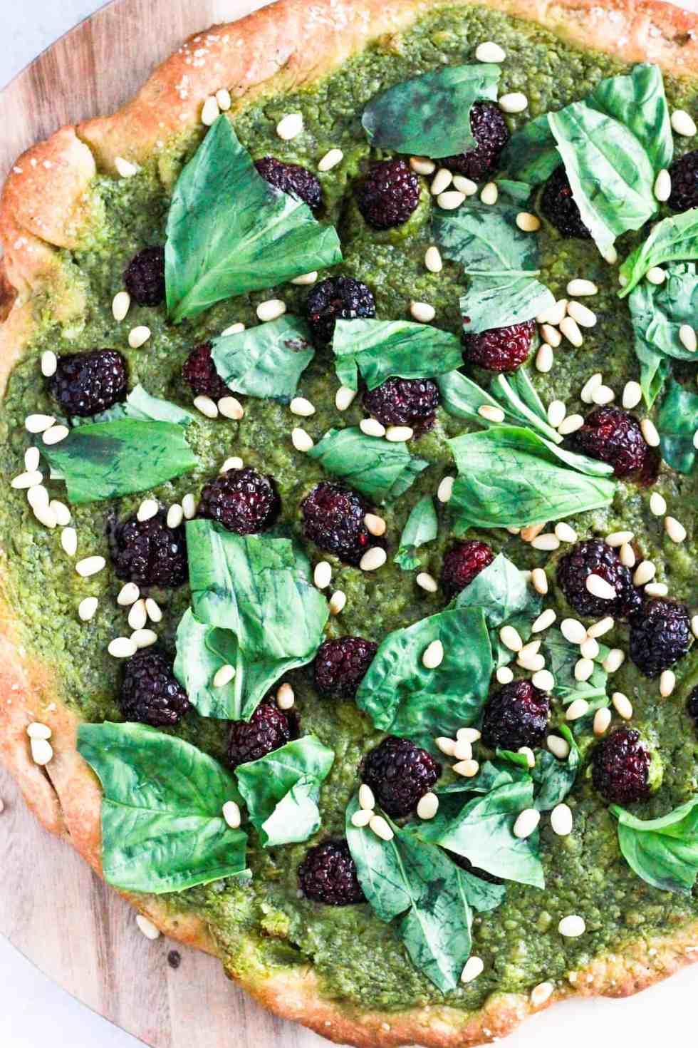 Green vegan pesto pizza on wood board.