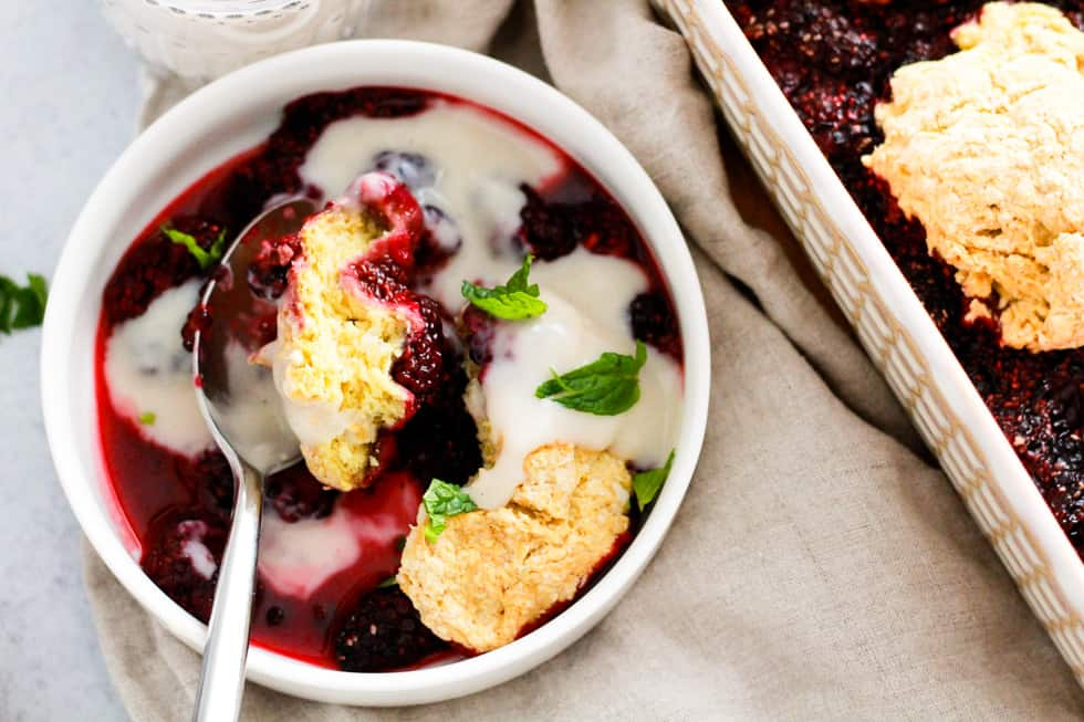 Horizontal image of berries, biscuit topping, and ice cream in a white bowl.