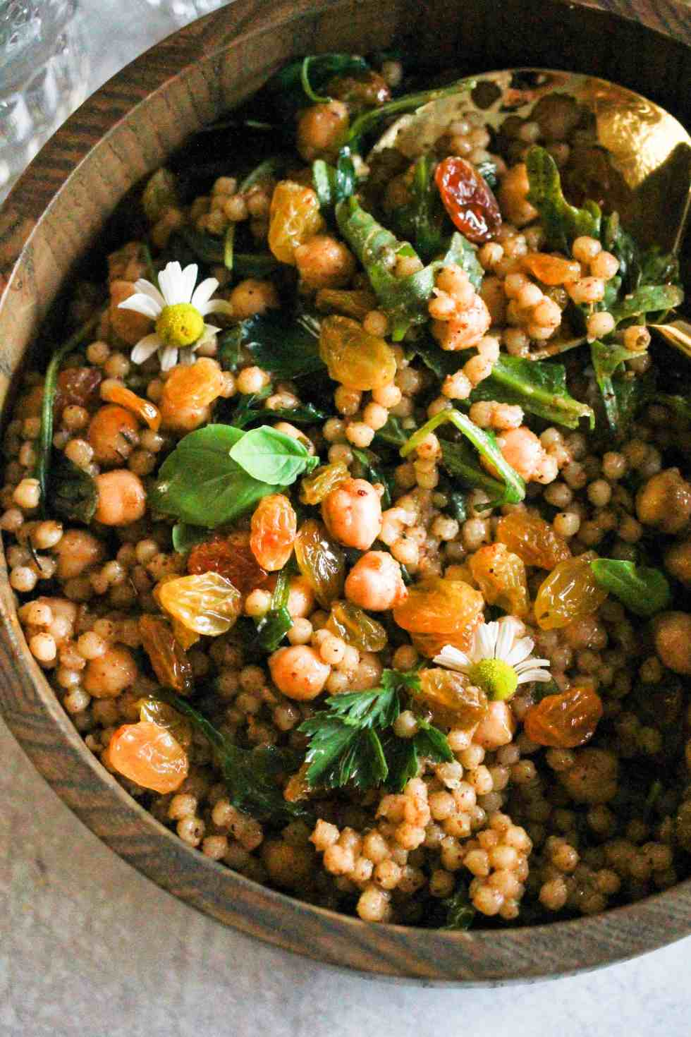 Closeup image of Israeli Couscous salad with chickpeas in a wooden bowl.