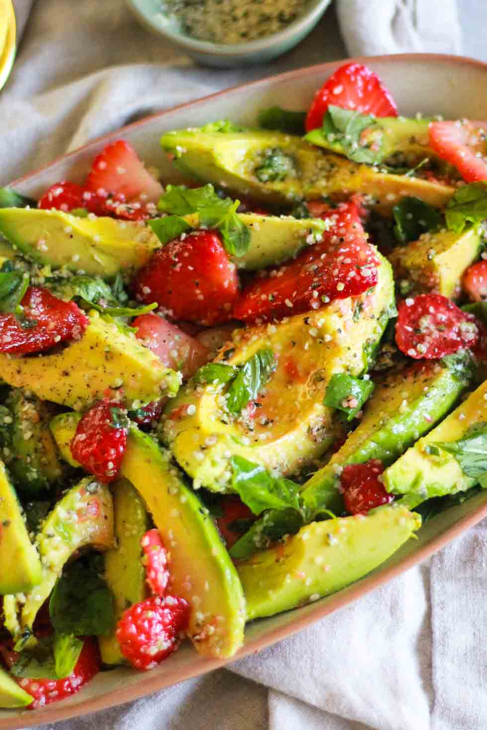 Closeup of Strawberry Avocado Salad on beige platter.